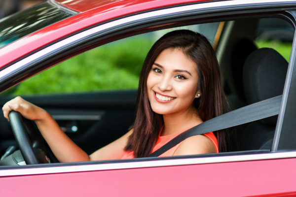 woman sitting in her new red car