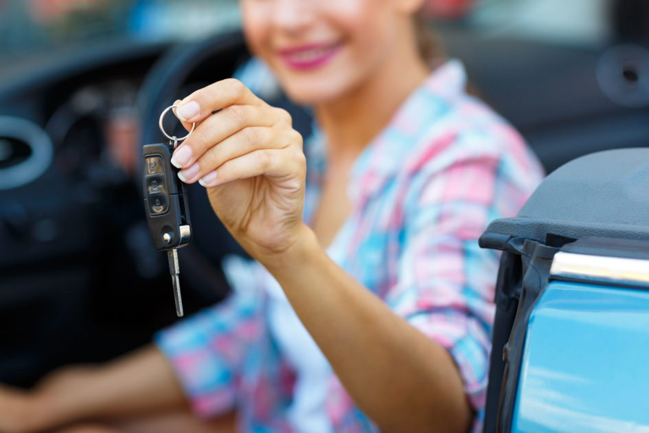 Woman holding a set of keys sitting in a car