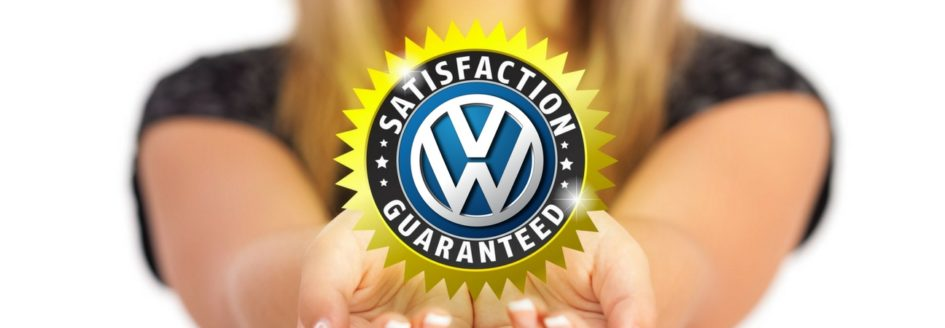 """A girl holding out a badge with """"VW"""" in the center and """"Satisfaction Guaranteed"""" around it referencing the extended Volkswagen warranty"""