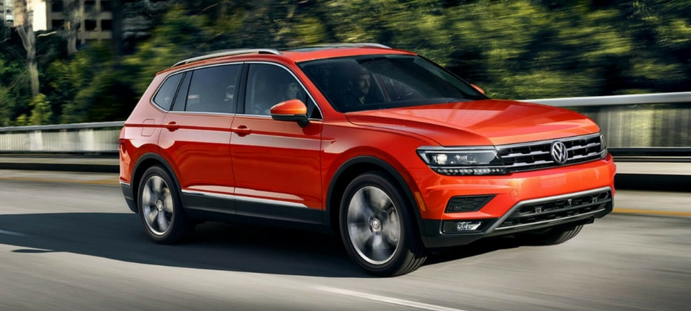 A red 2018 VW Tiguan driving down a road  in a blog about the Volkswagen Atlas and Tiguan