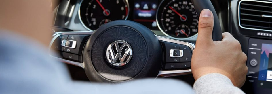 A close-up of a VW car steering wheel featured in a blog post about used vw cars