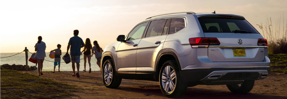 A 2019 Volkswagen Atlas parked at the beach while a family walks toward the water