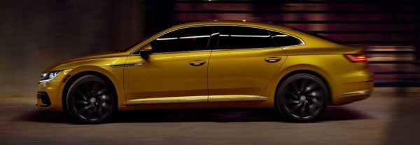 Golden 2019 Volkswagen Arteon driving through a dimly lit tunnel.